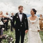 bride and groom walking in meddle of the people